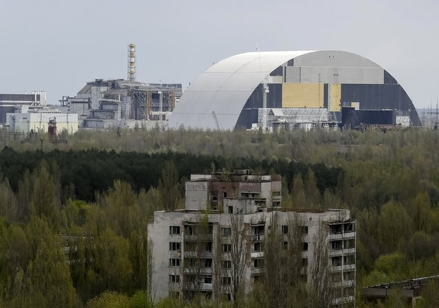 A containment shelter for the damaged fourth reactor (L) and the New Safe Confinement (NSC) structure (R) at the Chernobyl Nuclear Power Plant are seen from Ukraine's abandoned town of Pripyat, Ukraine, April 22, 2016. (Photo by Gleb Garanich/Reuters)