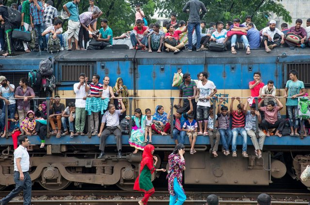 With no seats available inside, many commuters decide to take the risk and choose a rooftop view for their journey out of Dhaka. (Photo by Yousuf Tushar/Solent News & Photo Agency)