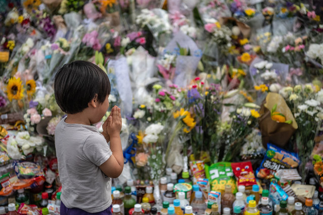 A little boy prays next to flowers laid at the scene of a knife attack on a group of schoolchildren, on May 29, 2019 in Kawasaki, Japan. An 11-year old girl and a 39-year-old man were killed by a knife-wielding man while at least 16 others were reportedly injured when the assailant attacked a group of elementary-school girls at a bus stop. The suspect, believed to be in his 50s, reportedly stabbed himself in the neck and died from his injuries. A motive for the attack has not yet been established. (Photo by Carl Court/Getty Images)