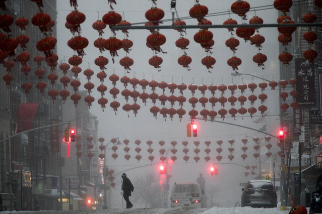 A pedestrian crosses East Broadway during a snowstorm, Tuesday, March 14, 2017, in the Chinatown neighborhood of New York. (Photo by Mary Altaffer/AP Photo)