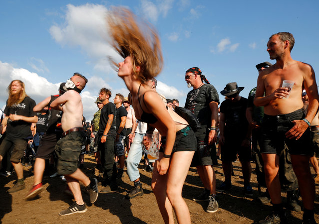 """A festivalgoer does """"head banging"""" during the performance of German death metal band Damnation Defaced at the world's largest heavy metal festival, the Wacken Open Air 2019, in Wacken, Germany on August 3, 2019. (Photo by Wolfgang Rattay/Reuters)"""