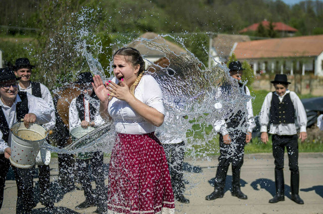 Young men pour water on young women, all dressed in folk costumes, in Ciko, some 180 km south of Budapest, Hungary, Monday, April 22, 2019. According to a several hundred years old tradition of Hungarian villages, young men pour water on young women who in exchange present their sprinklers with beautifully colored eggs on Easter Monday. (Photo by Tamas Soki/MTI via AP Photo)
