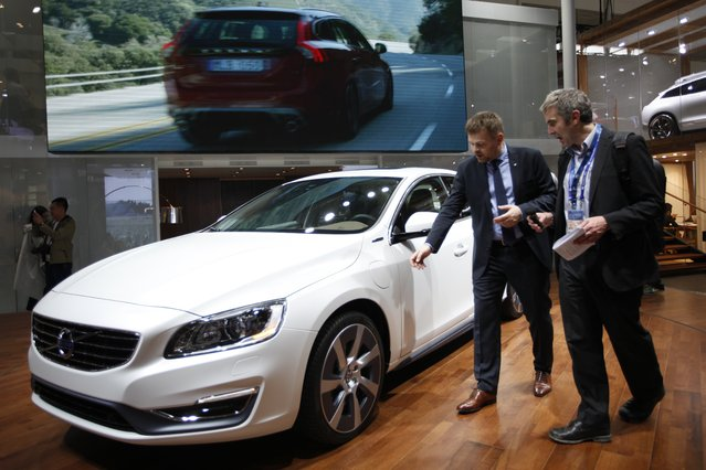 """Visitors check out a Volvo car on display at the China International Exhibition Center new venue during the """"Auto China 2014"""" Beijing International Automotive Exhibition in Beijing on April 20, 2014. (Photo by AFP Photo)"""
