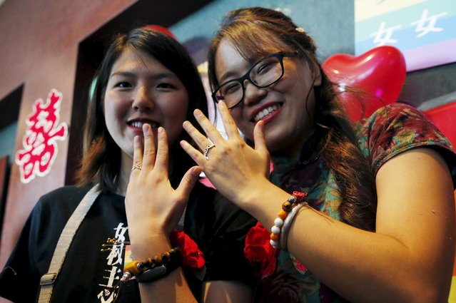 Li Tingting (L) and Teresa show their wedding rings at their wedding reception in Beijing, China July 2, 2015. Li, a 25-year-old prominent women's rights activist who was released from detention in April, held the wedding ceremony with her partner Teresa on Thursday and announced their marriage in an effort to push for LGBT (lesbian, gay, bisexual, and transgender) rights in China. (Photo by Kim Kyung-Hoon/Reuters)