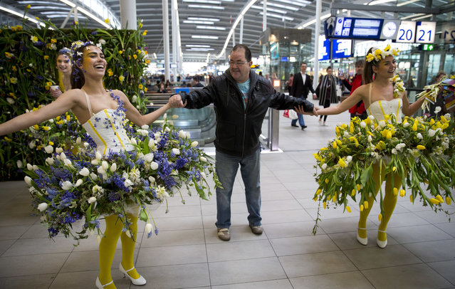 Models wear floral arrangements as they interact with travelers at Central Station in Utrecht, Netherlands, Wednesday, March 29, 2017. About 20,000 spring flowers were used to promote Keukenhof, the largest flower show in the world, and transport companies Arriva and NS. (Phoot by Peter Dejong/AP Photo)