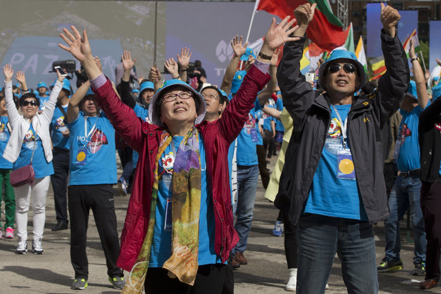 Chinese conglomerate Tiens Group employees wave during a celebration in Madrid, Spain, Friday, May 6, 2016. (Photo by Paul White/AP Photo)