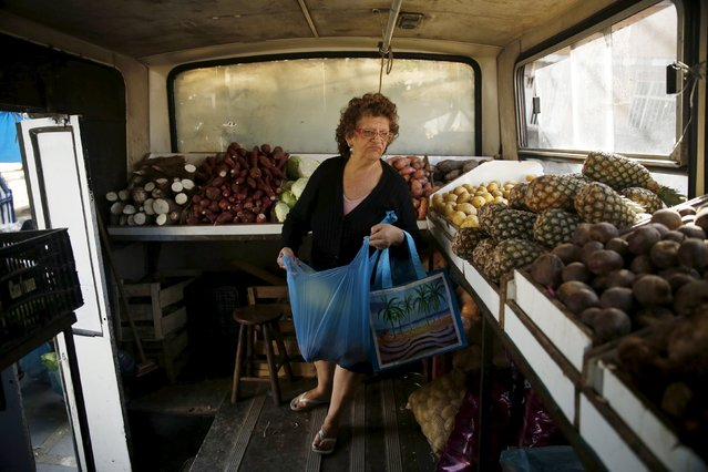 A woman looks for fruits to buy inside a bus called Sacolao in Santa Teresa neighborhood in Rio de Janeiro, Brazil, July 7, 2015. The bus, which began operating as a municipal initiative but has been taken over by a private enterprise, arrives every week in some neighborhoods to facilitate families with their grocery shopping and sells food at an affordable price, according to sellers. (Photo by Pilar Olivares/Reuters)