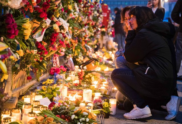Well wishers comfort each other as they place flowers at a makeshift memorial outside a department store in Stockholm on April 8, 2017. 4 people died and 15 was injured when a hijacked truck plunged into a crowd in a pedestrian shopping area in the Swedish capital on April 7, 2017. (Photo by Odd Andersen/AFP Photo)