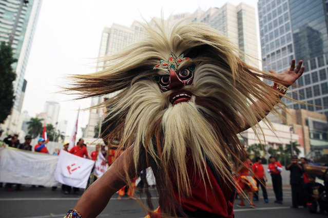 A masked dancer performs during a May Day rally at the business district in Jakarta, on May 1, 2014. (Photo by Reuters/Beawiharta)