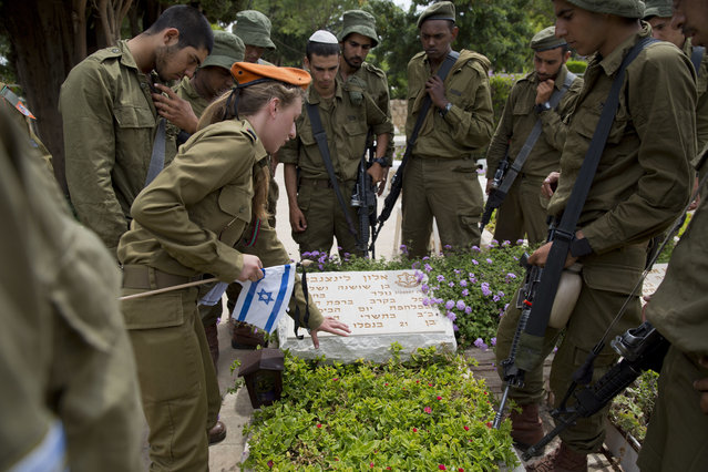 Israeli soldiers look at an officer explaining how to place a small flag with black ribbons on a grave of a fallen soldier on the eve of memorial Day in Kiryat Shaul military cemetery in Tel Aviv, Israel, Tuesday, May 10, 2016. (Photo by Ariel Schalit/AP Photo)