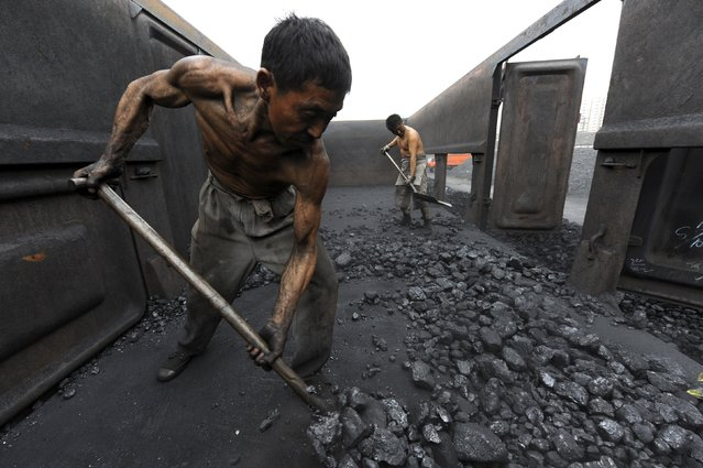 Workers unload coal at a storage site along a railway station in Hefei, Anhui province October 27, 2009. (Photo by Jianan Yu/Reuters)