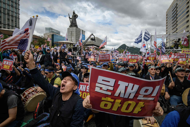 Anti-government protesters shout slogans and wave placards at a rally calling for president Moon Jae-in to step down, in central Seoul on October 3, 2019. Moon's approval rating recently hit a record low after he appointed a scandal-tainted ally as justice minister. (Photo by Ed Jones/AFP Photo)