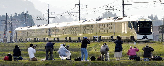 Rail buffs line up to take photos of East Japan Railway Co.'s luxurious Train Suite Shiki-shima (Four Seasons Island) running through the field in Nikko, northeast of Tokyo, Monday, May 1, 2017. JR East launched its 10-car all-suite sleeper train service Monday with only 17 rooms that can accommodate 34 passengers maximum for a four-day, three-night trip to popular tourist spots in Japan's northern areas including Kanto, Tohoku and Hokkaido. All the tickets have been sold out until March next year despite its high fare that ranges between 320,000 yen (US$3,360) for a two-day, one night trip and 950,000 yen ($9,980) for a four-day, three-night trip, according to the company. (Photo by Yoshitaka Sugawara/Kyodo News via AP Photo)