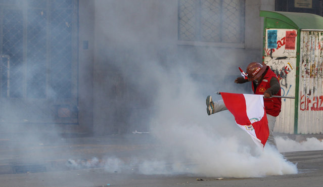 A miner kicks a can of tear gas shot by riot police, as he holds a Potosi department flag during a protest demanding more resources for his region, in La Paz, Bolivia, Friday, July 17, 2015. Residents in the capital city of Potosi have held a general strike over the past 11 days to pressure the national government to respond to their demands for a better hospital, an operable airport and a cement factory, among other things to revamp the economy. (Photo by Juan Karita/AP Photo)