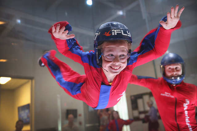 Flying instructor David Schnaible teaches wind tunnel flying to nine-year-old Liam Harrison at the iFly indoor skydiving facility in Rosemont, Illinois, on May 29, 2014. Guests at the facility are introduced to the sensation of free-fall skydiving as they are lifted into the air by fans which generate an upward draft from 80 to 175 miles per hour inside a 14-foot-wide circular chamber. (Scott Olson/Getty Images)
