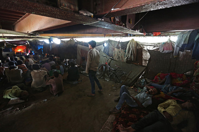 People watch a movie in a makeshift cinema located under a bridge in the old quarters of Delhi, India May 25, 2016. (Photo by Cathal McNaughton/Reuters)