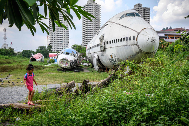 A child plays in front of abandoned aircraft in the suburbs of Bangkok on October 9, 2019. (Photo by Mladen Antonov/AFP Photo)