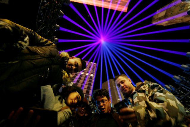 Visitors to the annual Vivid Sydney light festival stand beneath a moving spotlight show projected into the sky on the opening night of the light and sound show in Sydney, Australia May 27, 2016. (Photo by Jason Reed/Reuters)
