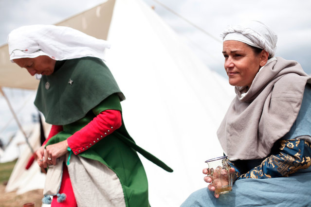 Women wearing Medieval garb attends a reenactment of the Battle of Agincourt, in Agincourt, northern France, Saturday, July 25, 2015. (Photo by Thibault Camus/AP Photo)