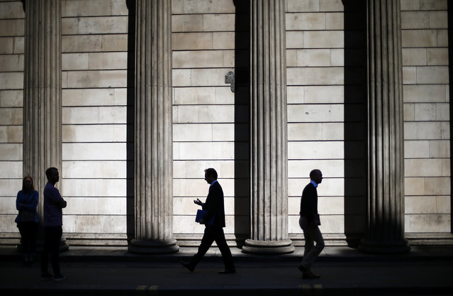 People are silhouetted on a sunny morning as they walk past the columns of the Bank of England in the City of London, May 19, 2014. Sterling eased on Monday, on growing talk the Bank of England will step in to cool the UK housing market, which would allow the central bank to keep interest rates lower for longer to sustain recovery elsewhere in the economy. (Photo by Andrew Winning/Reuters)