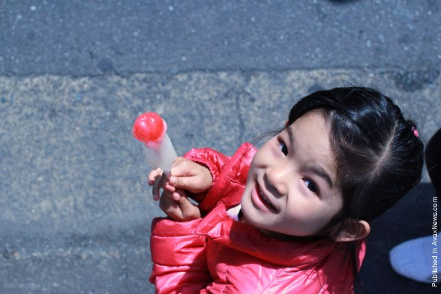 A Japanese young girl holds a phallic-shaped candy lollipop, as part of the Kanamara festival (Festival of the Steel Phallus), in the grounds of Wakamiya Hachimangu shrine, on April 1, 2012 in Kawasaki