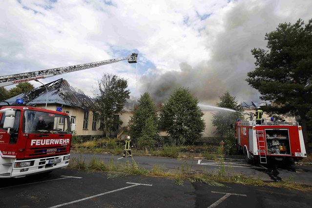 Firefighters pour water on a burning building after a fire broke out at a former U.S. airfield in Erlensee, Germany July 30, 2015. (Photo by Kai Pfaffenbach/Reuters)
