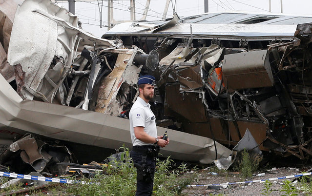 A police officer stands in front of the wreckage of a passenger train after it crashed into the back of a freight train in the eastern Belgian municipality of Saint-Georges-Sur-Meuse, June 6, 2016. (Photo by Francois Lenoir/Reuters)