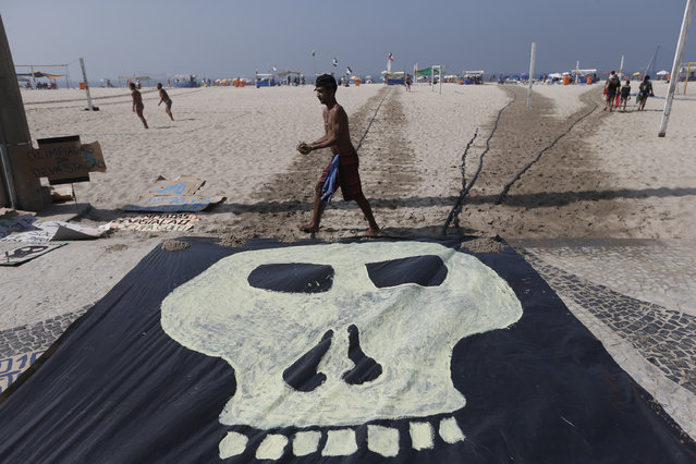 A man walks past a banner with a drawing of a skull symbolizing the death of nature during a protest on the Copacabana beach in Rio de Janeiro, Brazil, Saturday, August 1, 2015. Less than a dozen people showed up for a scheduled protest by environmentalists against the money spent in preparation for the Olympics and the construction of the game's golf course that was partially carved out of a nature reserve. (Photo by Silvia Izquierdo/AP Photo)
