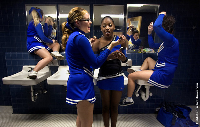 Palo Verde High School cheerleaders Ashley Gray, left and Gigi Tadeo use locker room sinks to give them a boost for applying makeup while sophomore cheerleader Virginia Bemer, center left, and sophomore dance team member Janelle Gary compare cell phone photos before getting on the bus to travel to Sahuarita for a football game