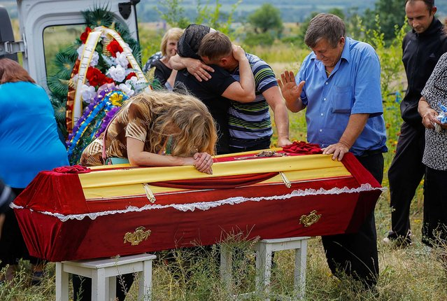 Relatives grieve at the coffin of pro-Russian fighter Dmitri Bystriukov, who was killed during a mortar attack, in the city of Krasnodon in Luhansk eastern Ukraine, on June 26, 2014. More than 300 people have been killed in eastern Ukraine in the past weeks as pro-Russian insurgents fought with government forces. (Photo by Dmitry Lovetsky/Associated Press)
