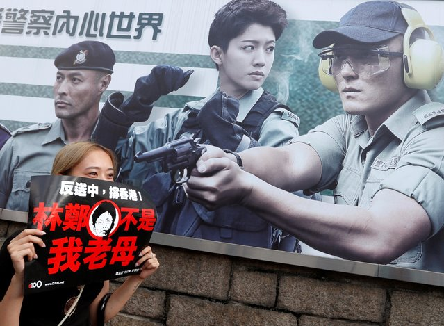 """A protester holds a placard next to a recruiting banner at the Hong Kong police headquarters reading """"Let yourself experience the feeling of being a police officer"""" as she attends a demonstration demanding Hong Kong's leaders to step down and withdraw the extradition bill, in Hong Kong, China, June 16, 2019. (Photo by Jorge Silva/Reuters)"""