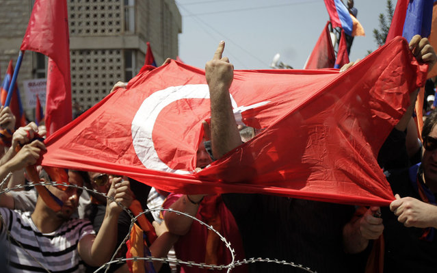 A Lebanese Armenian man gestures obscenely through a torn Turksih flag during a protest outside the Turkish embassy in Rabieh, northeast of Beirut, to commemorate the 97th anniversary of the Ottoman Turkish genocide against the Armenian people on April 24, 2012