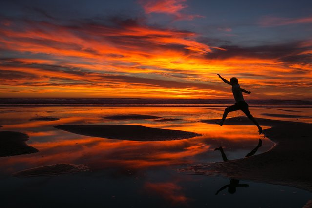 A brilliant sunset makes for a fun silhouette picture by jumping between sand bars at Shi Shi Beach on the Olympic Peninsula Friday July 17, 2015. (Photo by Bettina Hansen/The Seattle Times)