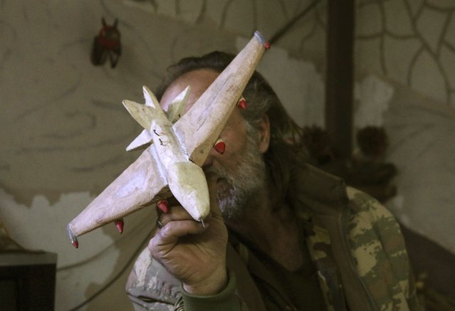 Abu Khalil, a 47-year-old Free Syrian Army fighter who is also a visual artist and decorator, poses with his carved wooden airplane at Jabal al-Turkman in Latakia province January 20, 2015. (Photo by Alaa Khweled/Reuters)