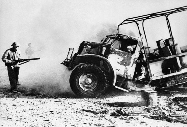 British soldiers cautiously approach an enemy supply truck which their guns set afire during recent action in the Western Desert, July 12, 1942. The vehicle was part of a supply column. (Photo by AP Photo)
