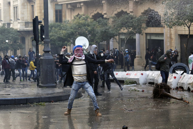 Anti-government demonstrators throw stones toward riot police at a road leading to the parliament building in Beirut, Lebanon, Saturday, January 18, 2020. (Photo by Hassan Ammar/AP Photo)