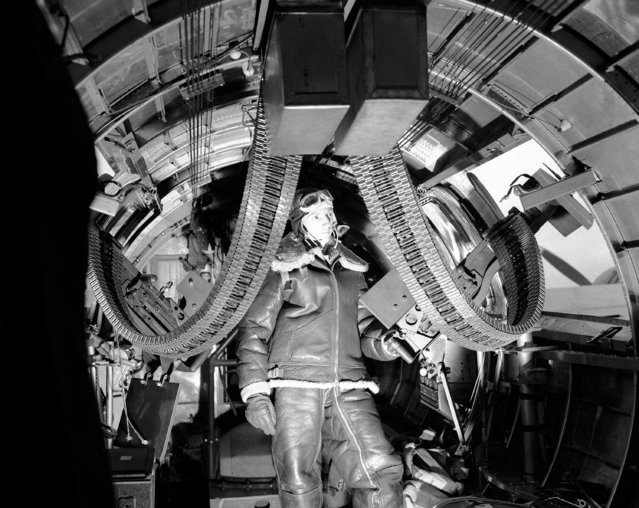 Sergeant William Ewing, side gunner and assistant radio operator inspects the feed belt of his gun,  on a Flying Fortress, at an airbase somewhere in England, on July 1, 1942. (Photo by AP Photo)