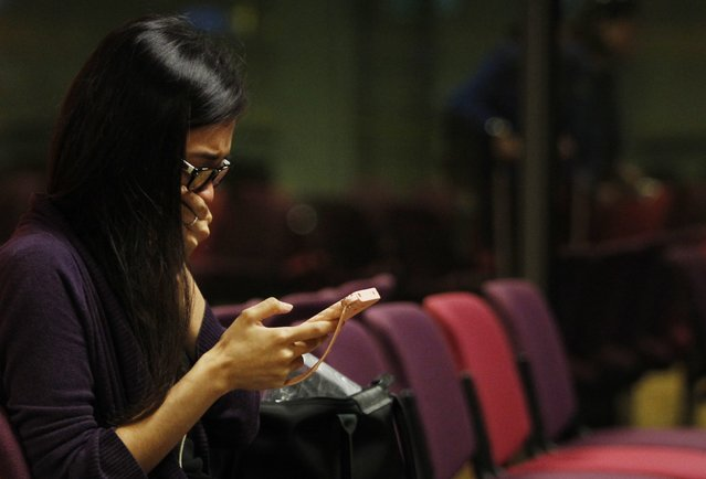 A Malaysian woman who had a relative on board the Malaysian Airlines MH17 reacts to messages on her mobile phone as she waits to travel to Kuala Lumpur International Airport from Singapore's Changi Airport July 18, 2014. The Malaysia Airlines Boeing 777 was brought down over eastern Ukraine on Thursday, killing all 295 people aboard and sharply raising the stakes in a conflict between Kiev and pro-Moscow rebels in which Russia and the West back opposing sides. (Photo by Edgar Su/Reuters)