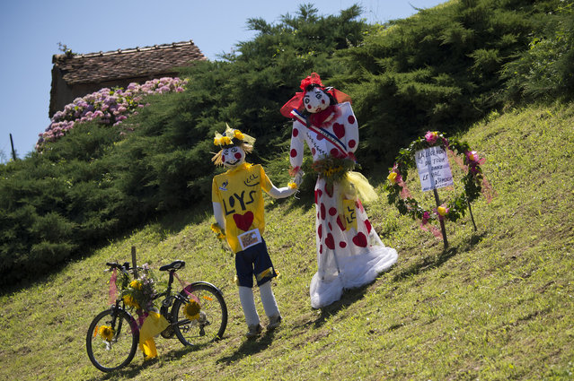 Mannequins wearing the overall leader's yellow jersey and the best climber's polka dot jersey are displayed along the road during the 187.5 km eleventh stage of the 101st edition of the Tour de France cycling race on July 16, 2014 between Besancon and Oyonnax, eastern France. (Photo by Lionel Bonaventure/AFP Photo)