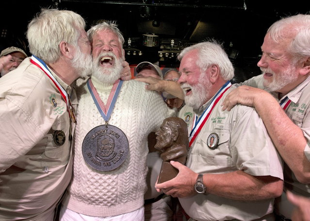 """Wally Collins(2nd-L) is congratulated after edging out 130 other contestants to win the 2014 """"Papa"""" Hemingway Look-Alike Contest late July 19, 2014, at Sloppy Joe's Bar in Key West, Florida. A Phoenix resident, Collins won the title on his sixth try during the event that attracted 131 entrants. Collins is surrounded by previous winners including, from left, John Stubbings, Gregg Fawcett and Charlie Bicht. (Photo by Andy Newman/AFP Photo/Florida Keys News Bureau)"""