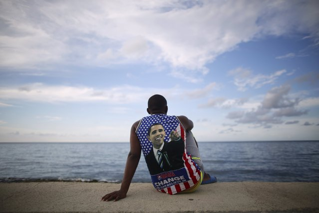 Medical student Electo Rossel, 20, wearing a shirt with a picture of U.S. President Barack Obama, listens to music at the Malecon seafront outside the U.S. embassy (not pictured) in Havana, Cuba, August 14, 2015. Watched over by U.S. Secretary of State John Kerry, U.S. Marines raised the U.S. flag at the embassy in Cuba for the first time in 54 years on Friday, symbolically ushering in an era of renewed diplomatic relations between the two Cold War-era foes. (Photo by Alexandre Meneghini/Reuters)