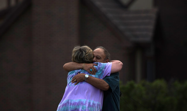 """Neighbors, who evacuated their homes from the encroaching Waldo Canyon fire, embrace after returning to their homes in Colorado Springs,on July 1, 2012. Residents began returning to charred areas of Colorado Springs on Sunday after the most destructive wildfire in Colorado history forced tens of thousands of people from their homes and left the landscape a blackened wasteland. The neighbors wished to stay unidentified due to """"jealous spouses,"""" they said. (Reuters/Adrees Latif)"""