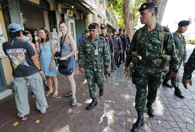 Military and police personnel walk past tourists as they patrol near the Grand Palace in Bangkok, Thailand, August 18, 2015. A bomb blast at a popular shrine in Bangkok that killed 22 people including eight foreigners did not match the tactics used by separatist rebels in southern Thailand, the country's army chief said on Tuesday. (Photo by Chaiwat Subprasom/Reuters)