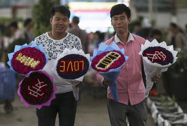 Men pose for pictures with bouquets they bought ahead of the upcoming Qixi Festival at a flower market in Kunming, Yunan province, August 1, 2014. Qixi, also known as the Double Seventh Festival and the Chinese version of Valentine's Day, falls on the seventh day of the seventh month in the Chinese lunar calendar. (Photo by Wong Campion/Reuters)