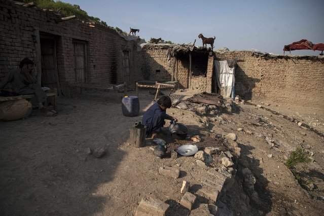 Samiullah, who says he is 14-years-old, washes dishes at a coal mine in Choa Saidan Shah, Punjab province, May 5, 2014. (Photo by Sara Farid/Reuters)