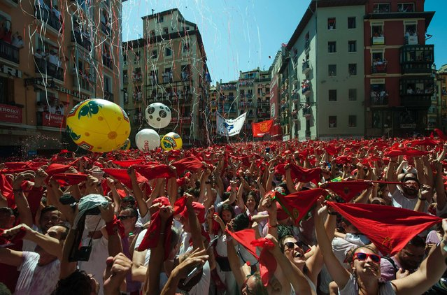 "Participants hold red scarves as they celebrate the ""Chupinazo"" (start rocket) to mark the kickoff at noon sharp of the San Fermin Festival, in front of the Town Hall of Pamplona, northern Spain, on July 6, 2016. The San Fermin festival is a symbol of Spanish culture that attracts thousands of tourist to watch the bull runs despite heavy condemnation from animal rights groups. (Photo by Miguel Riopa/AFP Photo)"