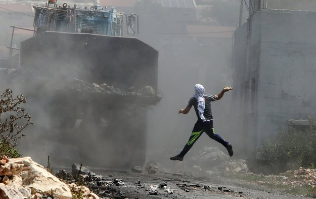 A Palestinian protester throws a bottle filled with paint at an Israeli army bulldozer during clashes following a demonstration against the expropriation of Palestinian land by Israel in the village of Kfar Qaddum, near Nablus in the occupied West Bank, on August 21, 2015. (Photo by Jaafar Ashtiyeh/AFP Photo)