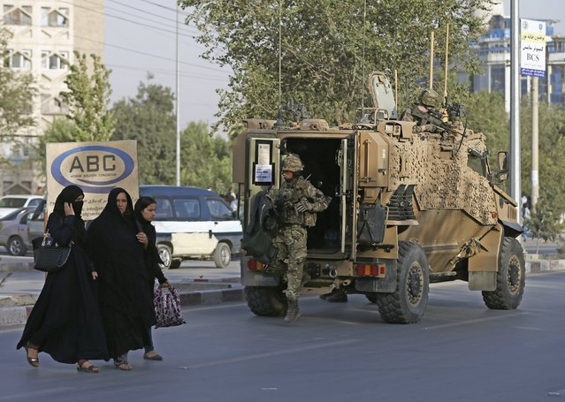 Afghan women walk as a British soldier arrives at the site of a blast in Kabul, Afghanistan August 22, 2015. A car bomb outside a Kabul hospital killed at least 10 people and caused widespread casualties among Afghan civilians, although it appeared to have targeted a vehicle carrying foreign citizens, witnesses and security sources said. At least one foreigner was among the 10 killed by the bomb that wounded 60 people, foreign ministry spokesman Wahidullah Mayar said. (Photo by Mohammad Ismail/Reuters)