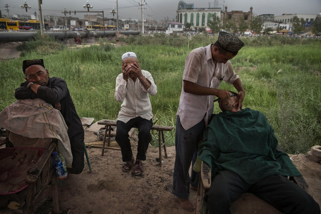 A Uyghur shaves a customer at an outdoor stall before the Eid holiday  on July 28, 2014 in old Kashgar, Xinjiang Province, China. (Photo by Kevin Frayer/Getty Images)