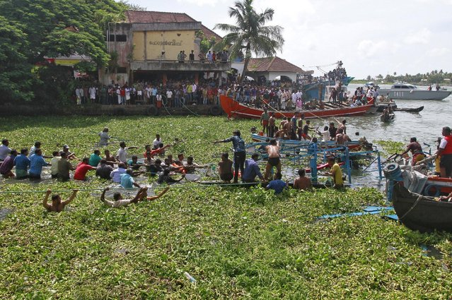 People pull ropes tied to a damaged ferry after it capsized in the waters of Vembanad Lake at Fort Kochi in the southern state of Kerala, India, August 26, 2015. At least six persons were killed on Wednesday when a ferry carrying around 30 people capsized after it was hit by a fishing boat in Vembanad Lake, police said. (Photo by Sivaram V/Reuters)